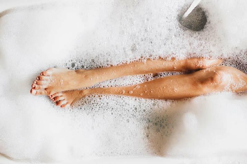 Donna nella vasca da bagno con acqua tiepida